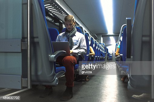 Young handsome man working on laptop while commuting to work