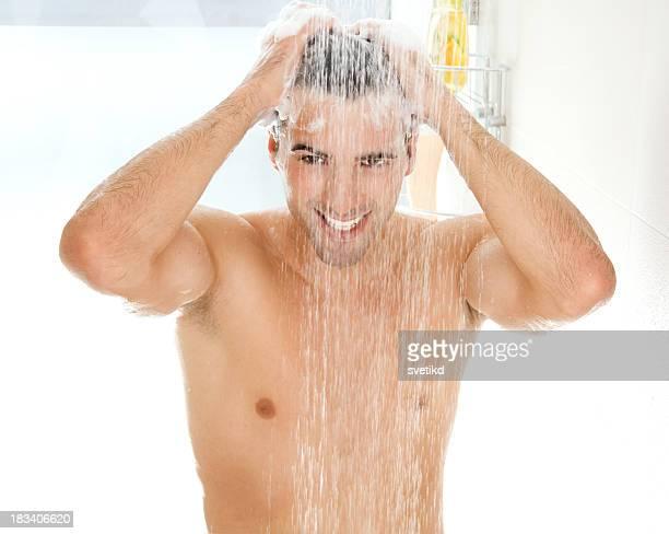Jovem bonito homens a tomar o duche.