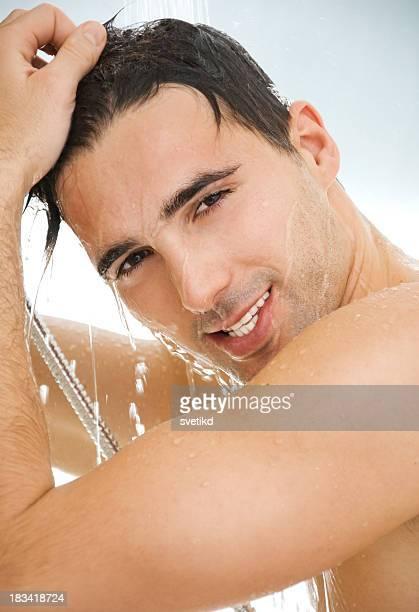 Junger gut aussehender Mann mit einer Dusche.