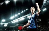 Portrait Of Young Man Celebrating Flawless Victory in Table Tennis On Dark Background with lights