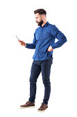 Young handsome well dressed business man surfing internet on smart phone. Side view. Full body isolated on white background.