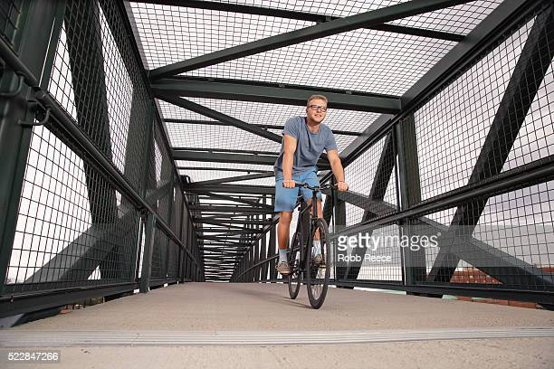A young, happy adult man riding his bicycle on an urban bridge