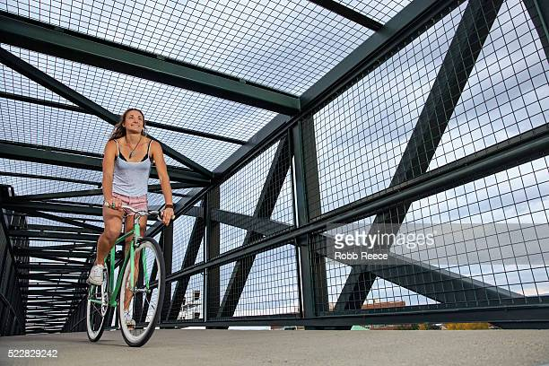 A young, happy adult woman riding her bicycle on an urban bridge