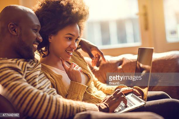 Young happy African American couple using laptop together.