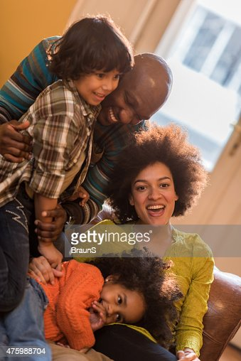 Young happy African American family having fun at home.