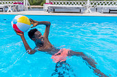 Young happy african american man playing with ball in swimming pool