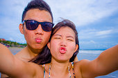 young happy and beautiful Asian Chinese couple taking selfie photo with mobile phone camera smiling joyful having fun on the beach in romance and lovers holidays trip picture concept