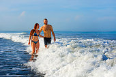 young happy and beautiful couple enjoying Summer holidays travel or honeymoon trip together in tropical paradise beach having fun relaxed and playful on the sea smiling cheerful