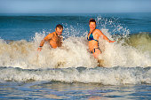 young happy and beautiful couple enjoying Summer holidays travel or honeymoon trip together in tropical paradise beach having fun relaxed and playful splashing on sea waves cheerful