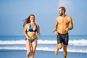 young happy and beautiful couple enjoying Summer holidays travel or honeymoon trip together in tropical paradise beach having fun running carefree and playful on the sea smiling cheerful
