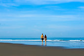 young happy and beautiful couple enjoying Summer holidays travel or honeymoon trip together in tropical paradise beach having fun walking relaxed and playful on the sea smiling cheerful