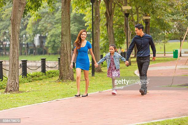 Young Happy Asian Family Walking Together in the Park