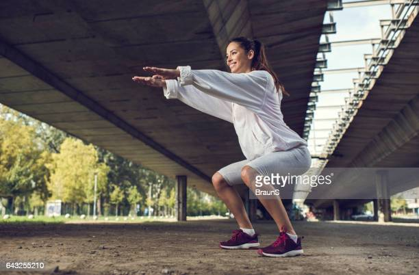 Young happy athletic woman exercising squats on the street.