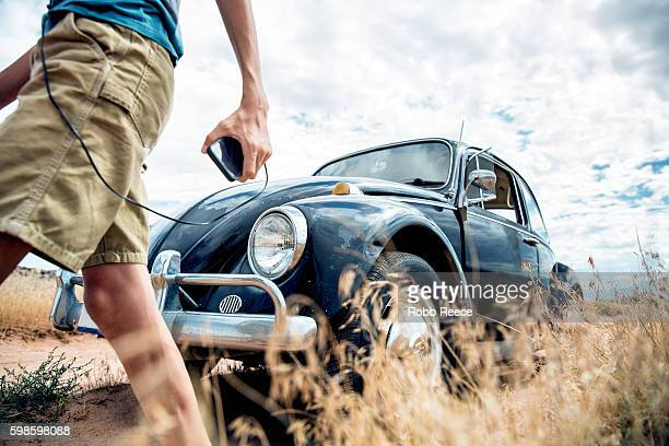A young, happy boy listening to music with a 1967 vintage Volkswagen Bug