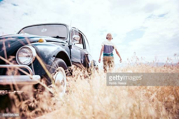 A young, happy boy walking near a 1967 vintage Volkswagen Bug
