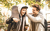 Young happy brothers having fun using mobile smart phones - Best friends sharing free time with new trends technology - Friendship concept with guys enjoying moments on smartphone device always online