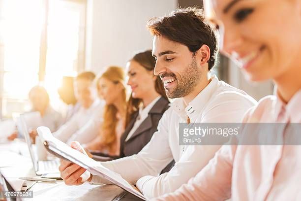 Young happy businessman reading reports on a meeting.