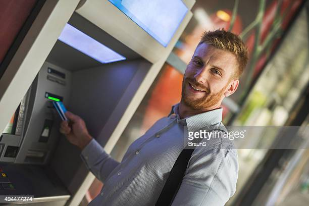 Young happy businessman removing cash from ATM.