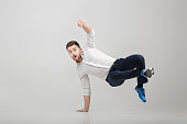 young happy businessman with beard in white shirt break dancing on grey background