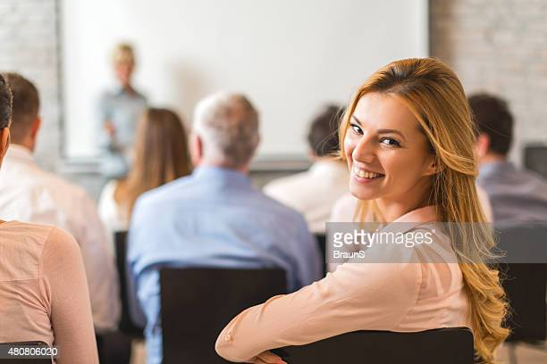 Young happy businesswoman attending a business education event.