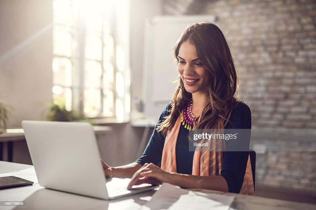 Young happy businesswoman working on laptop in the office. : Stock Photo