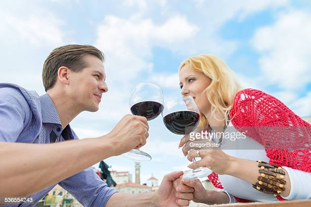 Young happy couple celebrating with red wine