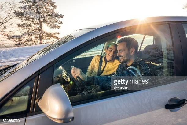Young happy couple going on a road trip during winter day.