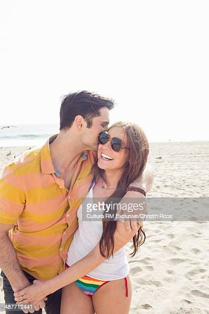 Young happy couple hugging on beach