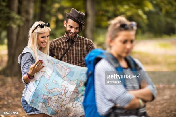 Young happy couple in nature reading a map together.