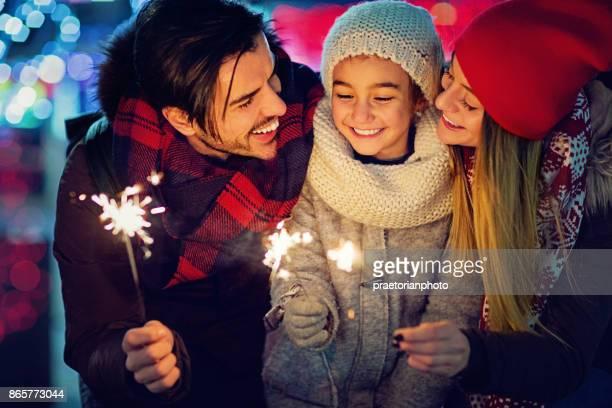 Jonge, gelukkige paar is knuffelen van hun dochter en houden van vuurwerk op Kerstmis