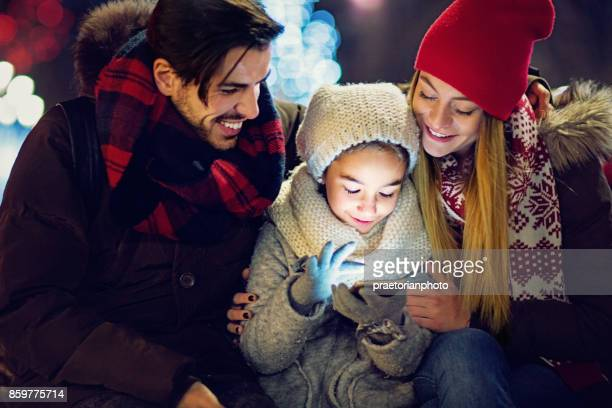 Joven, pareja feliz es abrazando a su hija hasta que ella está enviando mensajes de texto en Navidad