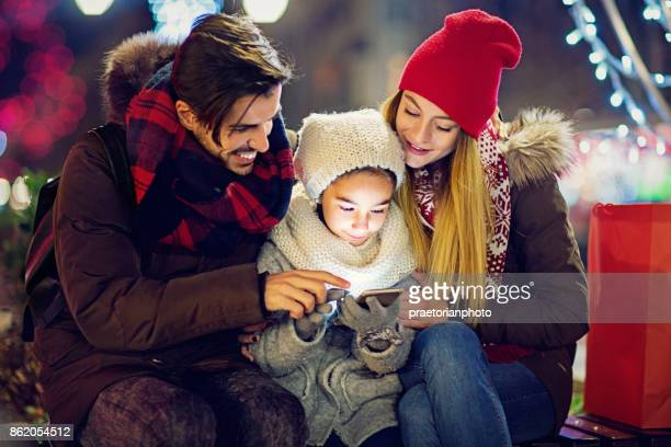Young, happy couple is hugging their daughter till she is texting at Christmas