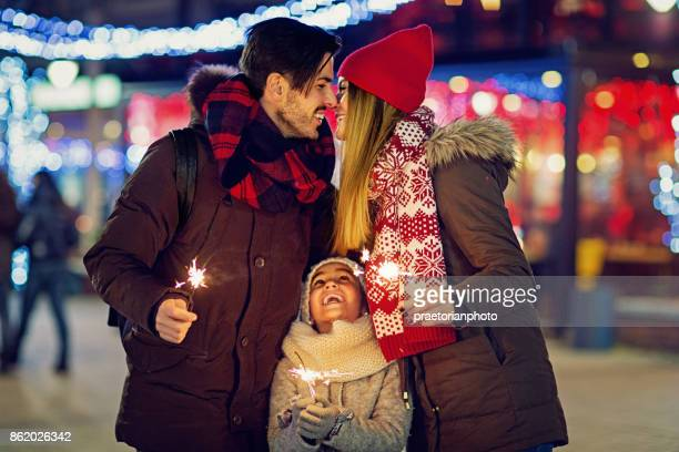 Young, happy couple is kissing and holding fireworks at Christmas