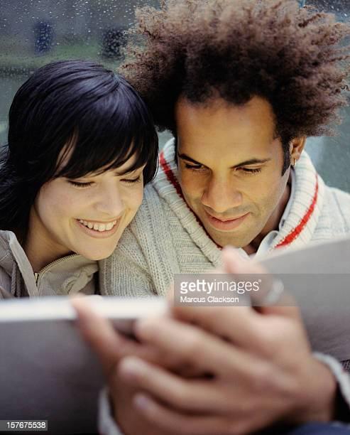 Junge Glückliches Paar, die ein Foto-album