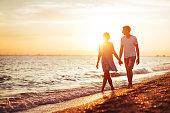 Young happy couple on seashore in the lights of sunset.