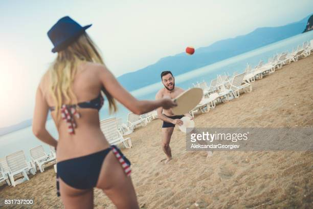 Young Happy Couple Play Beach Tennis Paddle Ball