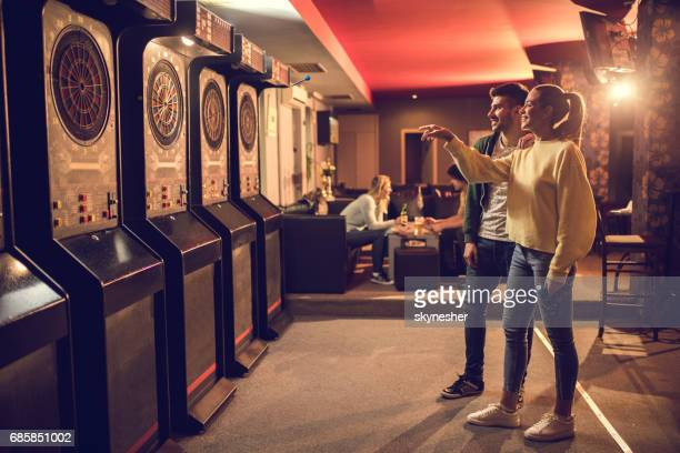 Young happy couple playing darts in entertainment club.
