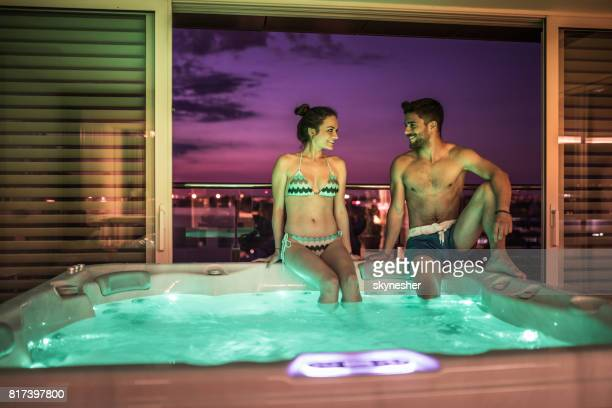 Young happy couple sitting on a hot tub and communicating.