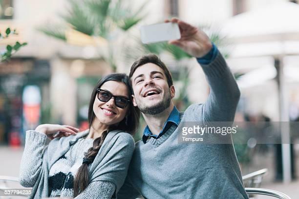 Jeune couple heureux prenant un selfie à Barcelone.