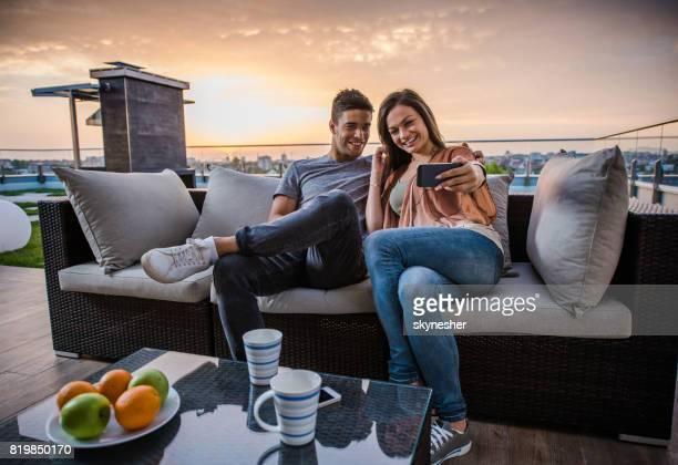 Joven pareja feliz teniendo un selfie en terraza al amanecer.