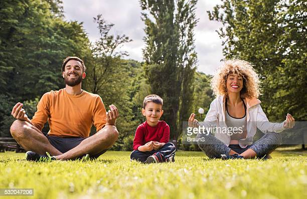Young happy family doing Yoga relaxation exercises on a grass.