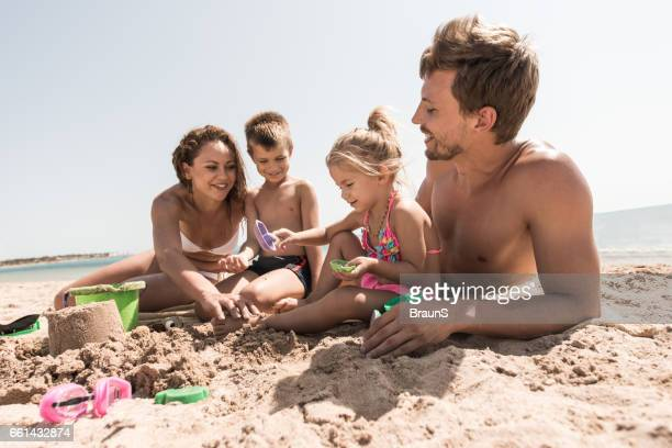 Young happy family playing with beach toys in sand.