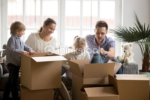 Young happy family with children packing boxes on moving day : Stock Photo
