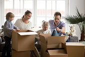 Young happy family with kids packing boxes on moving day together sitting on sofa in modern living room, kids with parents settling in new home, children helping to unpack stuff after relocation