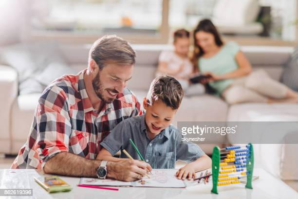Young happy father coloring with his little son at home.