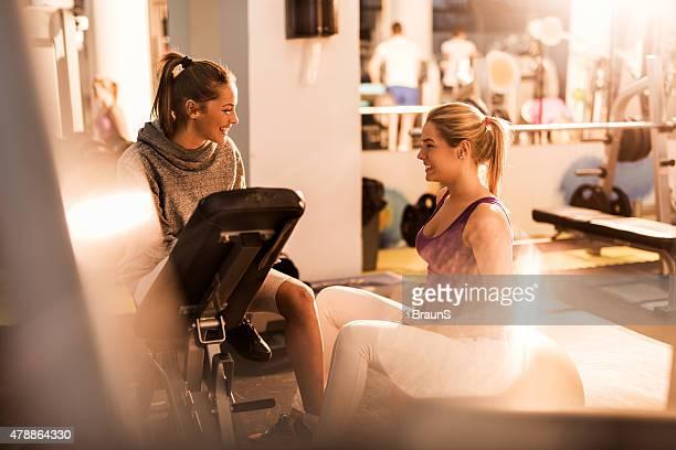 Giovane felice femmina gli amici parlando a vicenda in palestra.