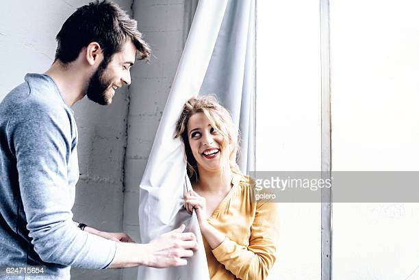 young happy french couple playing hide and seek with curtain