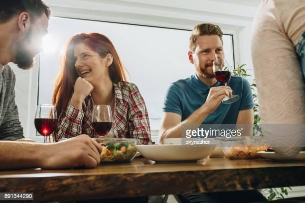 Unga glada vänner kommunicera under lunchtid hemma.