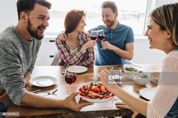 Unga glada vänner njuter i sin lunchtid på matbord.