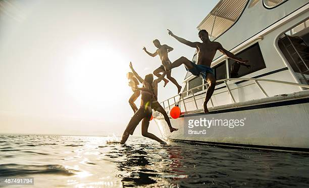 Young happy friends jumping from boat at sunset.